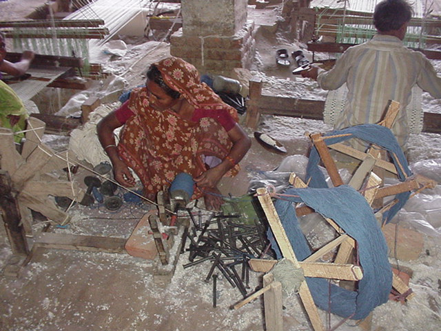woman making bonens for weft to weave floor rug